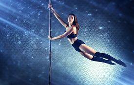 picture of light-pole  - Young slim pole dance woman flying on pole - JPG