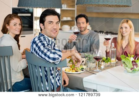 Group of friends eating at home. Portrait of happy young friends eating and drinking wine glass toge