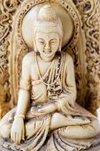 stock photo of siddhartha  - old little statue of buddha sitting in the meditation pose - JPG