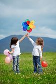 stock photo of children playing  - Cute happy children playing in spring filed - JPG