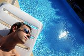 stock photo of nearly nude  - man taking sun near a swimming pool - JPG