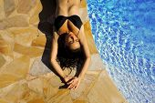 stock photo of nearly nude  - beautiful girl taking sun near to swimming pool - JPG