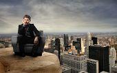 Постер, плакат: бизнесмен сидя в кресле на вершине здания города Нью Йорка