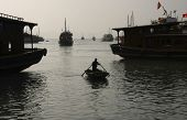 small transfer boat between the bigger tourist boats in Ha Long Bay, Vietnam poster
