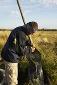 pic of shadoof  - man pouring water from bucket to drinking bowl for cattle  - JPG