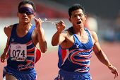 MALAYSIA - AUGUST 15: Thailand's blind athlete Kitsana Jorchuy runs with a guide at the track and fi