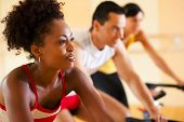 stock photo of cardio exercise  - three people in the gym exercising on cycles - JPG