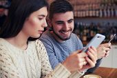 Closeup shot of affectionate couple looking photos on phone poster