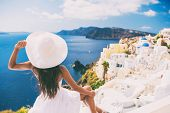 Tourist woman at view of Santorini cruise travel. Beautiful white village of Oia with Caldera and me poster