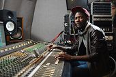 Modern young singer in rapper attire working in audio studio by recording equipment poster