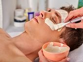 Mud facial mask of woman in spa salon. Massage with clay full face. Female lying wooden spa bed. Bea poster