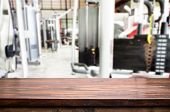Wooden Table On Blurred Background Of Fitness Gym Interior Of Modern Club With Equipment For Your Ph poster