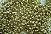 stock photo of gold glitter  - Celebratory brilliant beads of golden and white color horizontally  - JPG