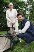 stock photo of 55-60 years old  - Senior with gardener and lawnmower - JPG
