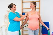 Pregnant woman working out with physical therapist and resistance band poster