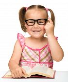 stock photo of cute little girl  - Cute little girl wearing glasses is flipping over pages of a book isolated on white - JPG