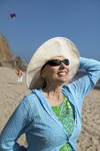 foto of early 50s  - Woman Enjoying Sunlight on Her Face at Beach - JPG