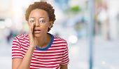 Beautiful young african american woman wearing glasses over isolated background hand on mouth tellin poster