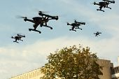 Swarm Of Unmanned Aircraft System (uav) Quadcopters Drones In The Air Over City poster