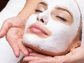 Spa massage for young woman with facial mask on face poster