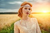 Romantic young woman with beautiful red hair walking in a golden wheat field. Beauty, fashion. Moder poster
