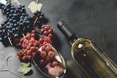 White Wine Bottle, Wineglasses, Fresh Grapes And Leaves On Black Wood Background. Flat Lay, Top View poster