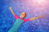 Portrait Of Calm Girl Relaxing In Clear Blue Water Of Outdoors Sunny Swimming Pool. Child In Goggles poster