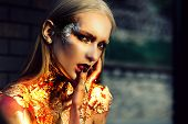 Golden Witch. Beauty Fashion Halloween Girl With Golden Make Up. Halloween Lady With Holiday Glamour poster