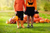 Kids With Pumpkins In Halloween Costumes poster
