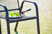 Tennis racket and tennis ball on chair poster
