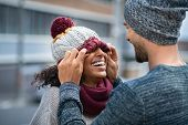 Loving multiethnic couple having fun outdoor in winter. Young man covering eyes his girl with woolen poster
