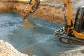 A Yellow Excavator Moving Gravel In The Foundation In The House Poles On Gravel poster