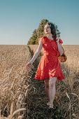 Happy Young Woman In Red Dress With Bread And Loafs In Net Grocery Bag On Wheat Field Sun Background poster