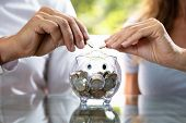 Mid-section Of Couple Inserting Coin In Transparent Piggybank poster