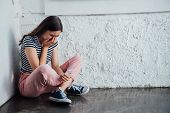 Sad Crying Girl In Pink Pants Sitting Near Wall And Holding Smartphone poster