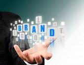 Businessman hand holding with blue brand alphabet . poster