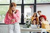 Group Of Schoolchildren Bullying Sad Girl With Smartphone poster