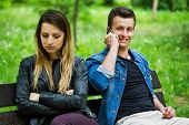 Man Smiling While Talking On Phone. His Girlfriend Looking Down Upset poster