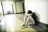 stock photo of forlorn  - a teen aged boy sits looking depressed in a hallway - JPG