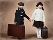 stock photo of old suitcase  - Cute little boy and girl are standing with their old suitcases - JPG