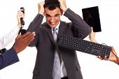 stock photo of multitasking  - frustrated businessman around by multiple office tools - JPG
