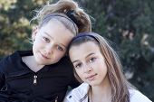 stock photo of bff  - Portrait of two young sisters outside in a park - JPG