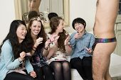 stock photo of partially clothed  - Cheerful young women enjoying while male stripper performing - JPG