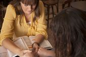 stock photo of compassion  - Two women hold hands and pray as they study the bible - JPG