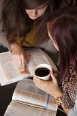 pic of scriptures  - Two young women study the bible together while drinking coffee.