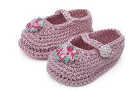 foto of mary jane  - Pink crochet baby booties with flowers isolated on white Hand - JPG