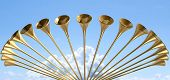 picture of glorious  - A group of golden medieval trumpets in a circular arc proclaiming a special heavenly occasion on light blue cloudy sky background - JPG