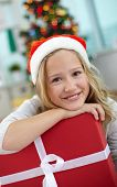 Portrait of cheerful girl with red giftbox looking at camera on Christmas evening