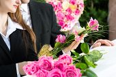stock photo of coffin  - Mourning man and woman on funeral with pink rose standing at casket or coffin - JPG