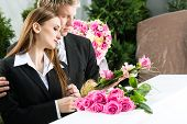 foto of funeral  - Mourning man and woman on funeral with pink rose standing at casket or coffin - JPG